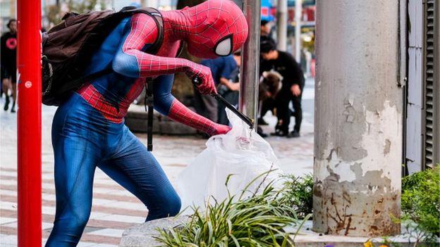 Örümcek adam kostümüyle temizlik yapan bir Japon.