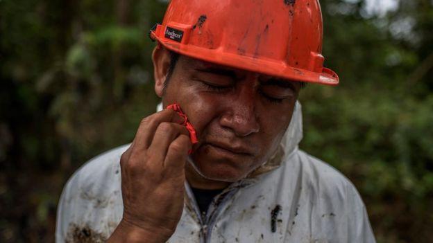 Hombre limpiándose el petróleo de la cara.