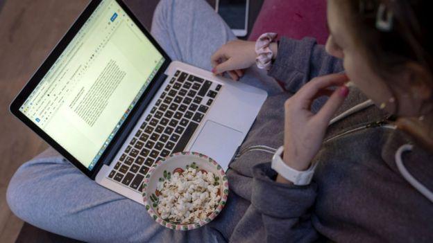 Louisa, 13, comendo pipocas enquanto faz lição de casa