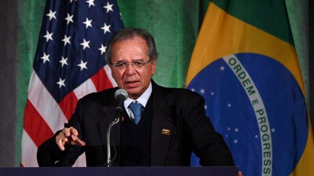 Guedes fala em púlpito durante evento nos EUA, com bandeira deste país e do Brasil no pano de funda
