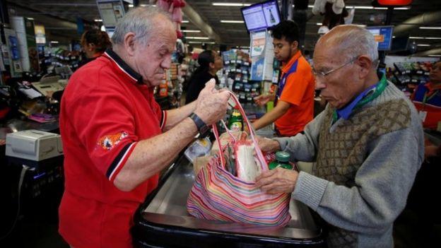 Un hombre empaca sus compras en una bolsa ayudado por otro