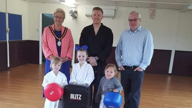Gavin posing with three young children and two other adults in the martial arts centre