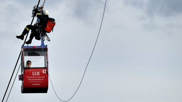 German fire crews evacuate dozens of passengers from suspended cable cars that run over the river Rhine after a gondola ran into a support pillar in Cologne, Germany, 30 July 2017