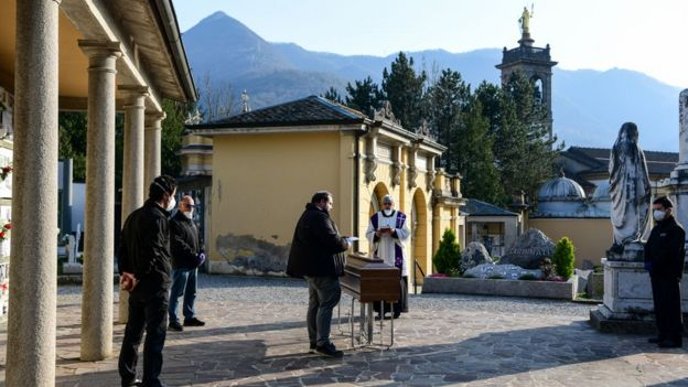 A priest celebrates funeral service without relatives inside the cemetery of Zogno, near Bergamo, northern Italy, on March 21, 2020