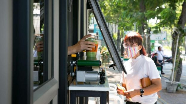 Uma mulher na Tailândia recebe sua bebida de um vendedor a uma distância segura, graças a uma esteira automática