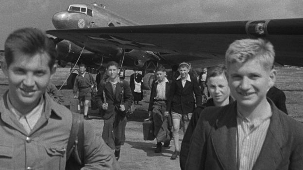 Survivors arriving in the UK with an aeroplane in the background