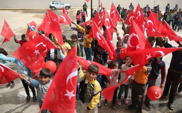 احتفال الأطفال وهم رافعين العلم التركي، مع غياب الأعلام السورية، في إحدى قرى عفرين بعد سيطرة الجيش التركي والفصائل الموالية له. 26 مارس/آذار 2018