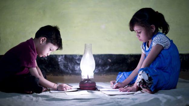 Dos niños haciendo tarea con una lámpara.