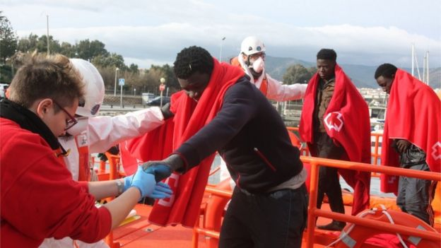 Spanish Red Cross workers help illegal migrants that were rescued off the Strait of Gibraltar, upon their arrival at the port of Algeciras, Cadiz, southern Spain, 9 January 2018