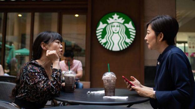 Dos mujeres toman un café en un Starbucks.