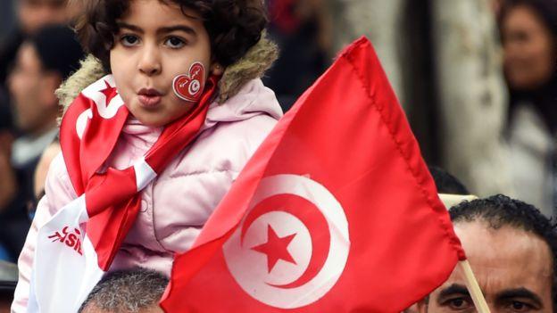 طفلة تمسك علم تونس على أكتاف أبيها