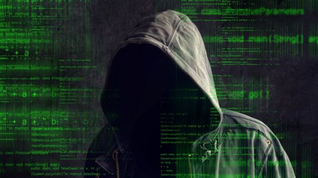 A person with a hood, against a background of computer codes.