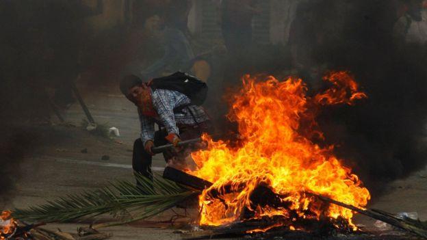 Un manifestante junto a una barricada incendiada en Nochixtlán