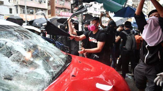 Người biểu tình tấn công chiếc xe taxi đâm vào đoàn người biểu tình làm bị thương cả hai chân của một cô gái hôm 6/10.