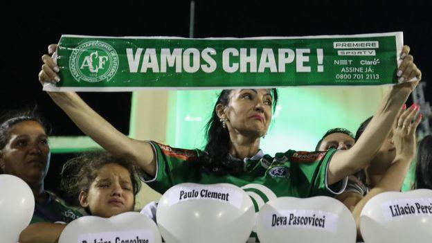 Mujer con un cartel que dice Vamos Chape durante la vigilia en el estadio del club