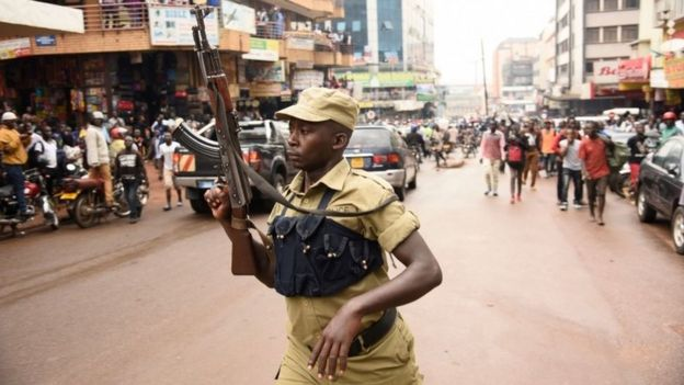 An Ugandan police officer lifts his AK-47 riffle aloft opposite protesters during a demonstration on July 11, 2018 in Kampala to protest a controversial tax on the use of social media