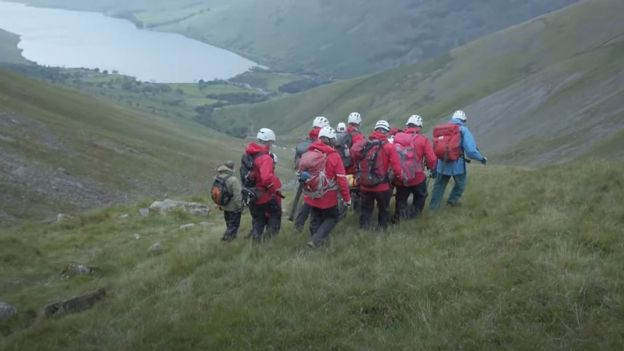 Six rescuers carry stretcher with Daisy on it overlooking lake