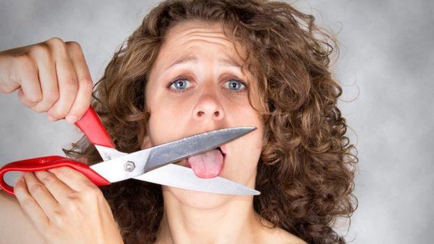 Una mujer que se va a cortar la lengua con una tijera