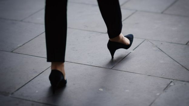 Woman's feet avoiding crack on pavement