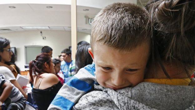 Niño migrante es cargado por su mamá