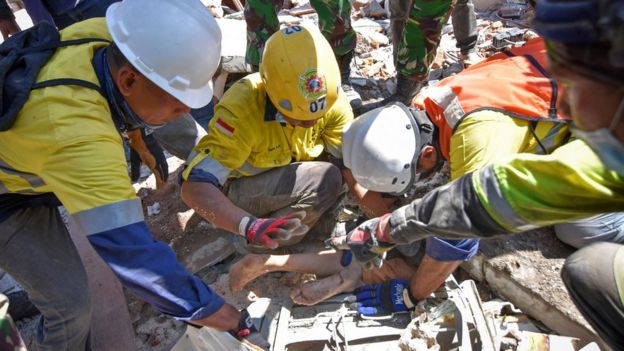 Rescue workers remove a woman alive from the rubble of a building in Tanjung, North Lombok (7 Aug 2018)