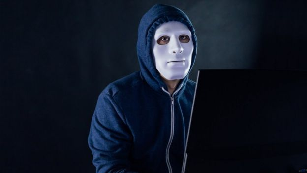 A man in a mask behind a laptop