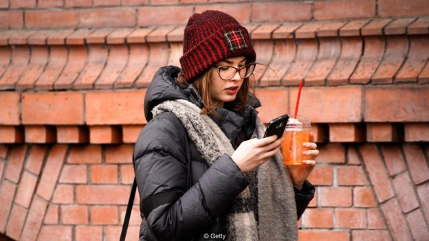 Imagem mostra mulher agasalhada usado smartphone com uma mão e segurando um copo com a outra