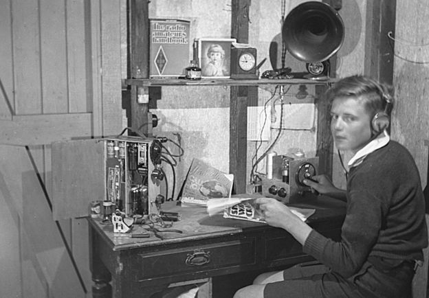 David pictured as a boy, wearing headphones and using his radio equipment
