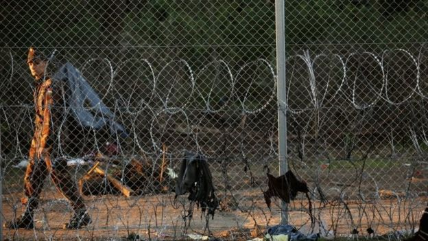 A Hungarian soldier patrols the razor wire fence at the Hungarian border with Serbia (12 September 2015)