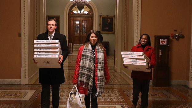 Three young people carry pizzas through the corridors of the US Capitol Building in this photo taken late on Thursday night