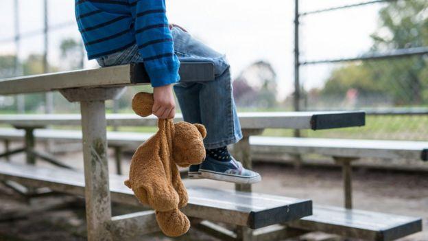 Foto ilustrativa sobre abuso infantil - menino sentado em arquibancada com ursinho de pelúcia