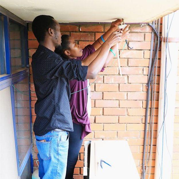 Integrantes de sensors.AFRICA instalando un monitor de la calidad del aire