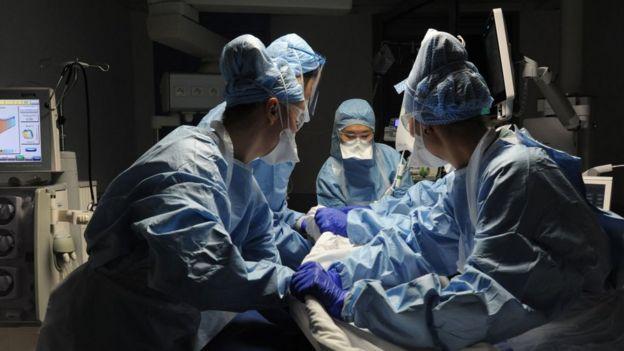 Profissionais de saúde atendem paciente na maca de hospital