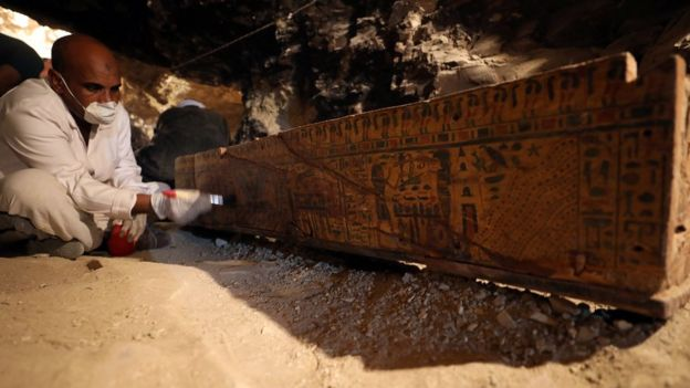 Egyptian antiquities worker brushes a coffin in a recently discovered tomb of Amenemhat, a goldsmith from the New Kingdom at the Draa Abu-el Naga