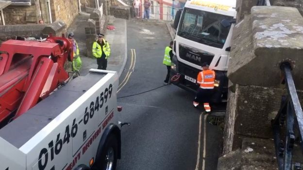 House damaged after lorry gets stuck on steep bend - BBC News