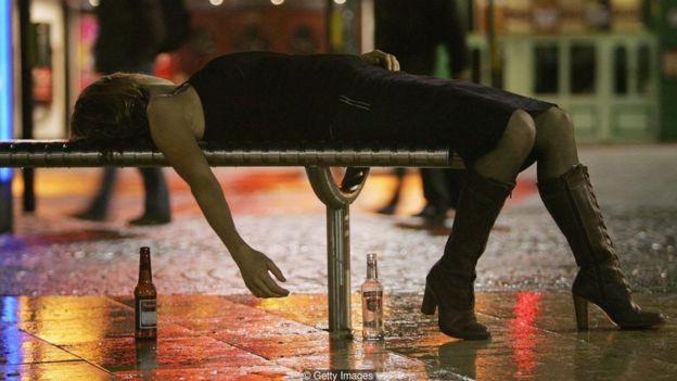 Mulher deitada no banco com garrafa de cerveja ao lado