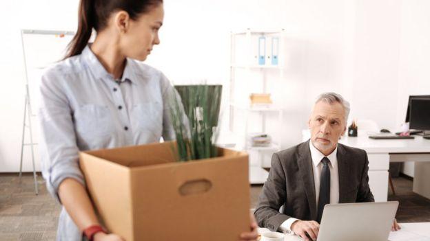 Una mujer con una caja con pertenencias mira de reojo a un hombre sentado en un escritorio.
