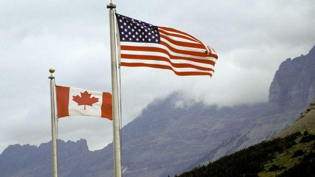 Banderas de Canadá y Estados Unidos ondean en un parque nacional de Montana