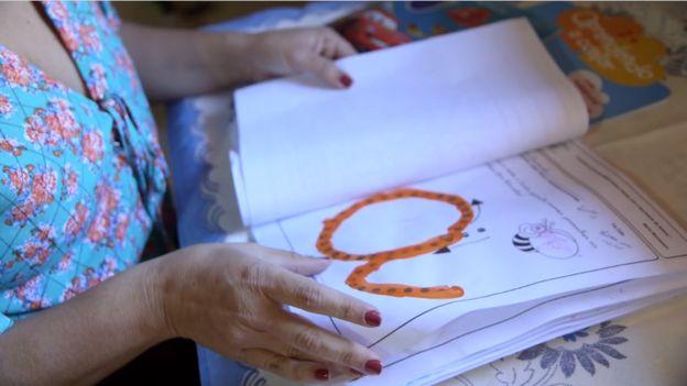 Elise vendo desenhos do filho