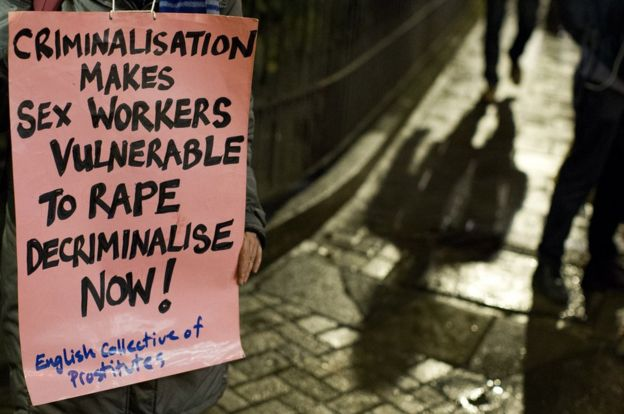A protester holds a placard during a candle lit vigil to mark the international day to end violence against sex workers, organised by the English Collective of Prostitutes
