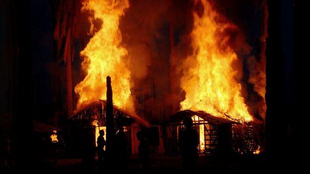صورة من الفيلم تعيد تصوير احتراق المنازل في أحد المجازر في قرية كامبونغ كولام