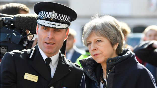Theresa May con un agente de policía.