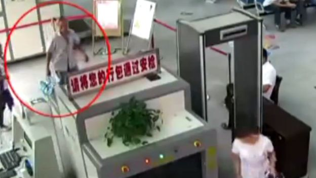 Mr Zheng seen on CCTV putting his bag through a security scanner