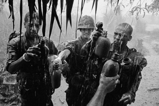 Soldiers capture rainwater in their flasks