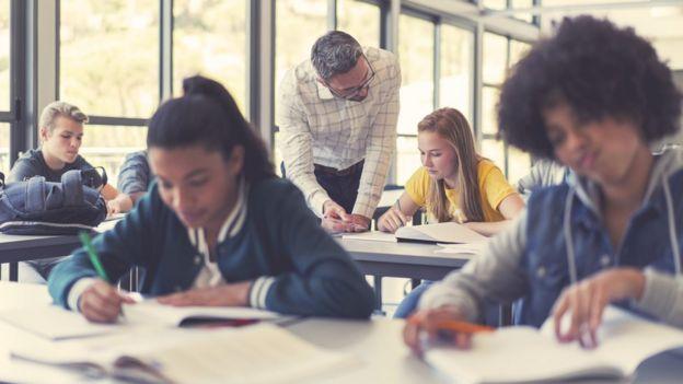 Estudiantes en un aula con libros.