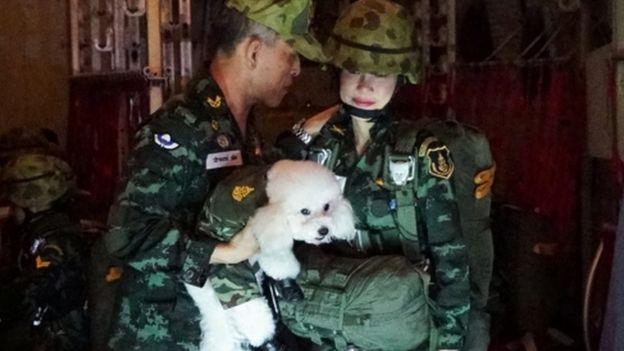 Thai King Maha Vajiralongkorn (L) holding a poodle next to royal consort Sineenat Wongvajirapakdi (R)