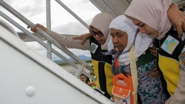 Seorang calon jemaah haji dipapah petugas saat keberangakatan sebelum pandemi covid-19.