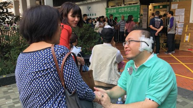Andrew Chiu, a candidate in Hong Kong's district council elections in November 2019, sat outside a polling station chatting to voters