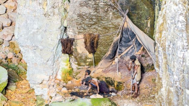 Un modèle représentant la vie primitive dans les grottes : un groupe d'hominidés cuisinent près d'un feu et dessèchent les peaux.