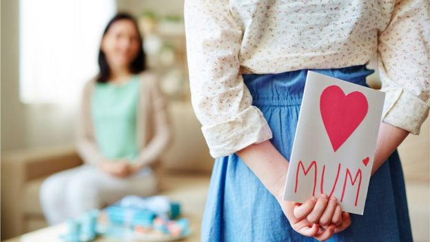 Una niña con una tarjeta hecha a mano para su madre